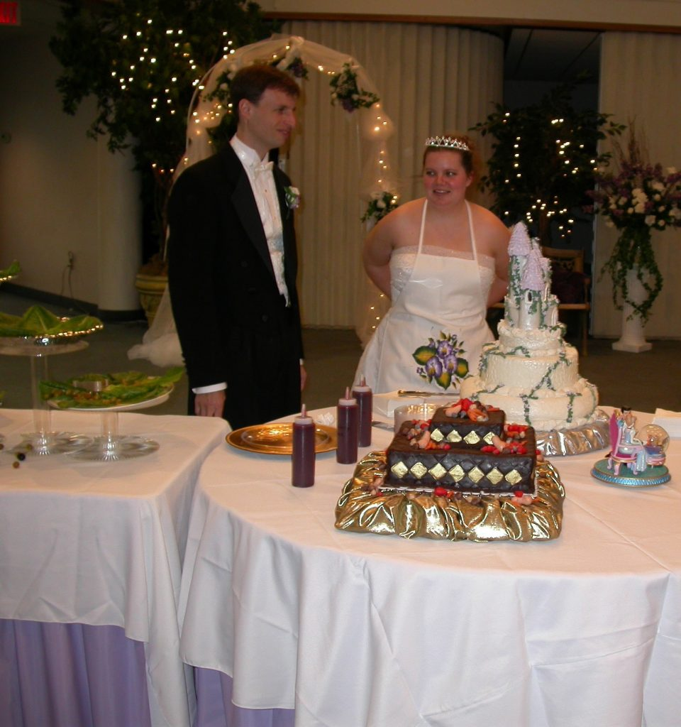 Chris and Karen standing behind the table holding their bride and groom cakes. Karen is tying an apron around her waist.